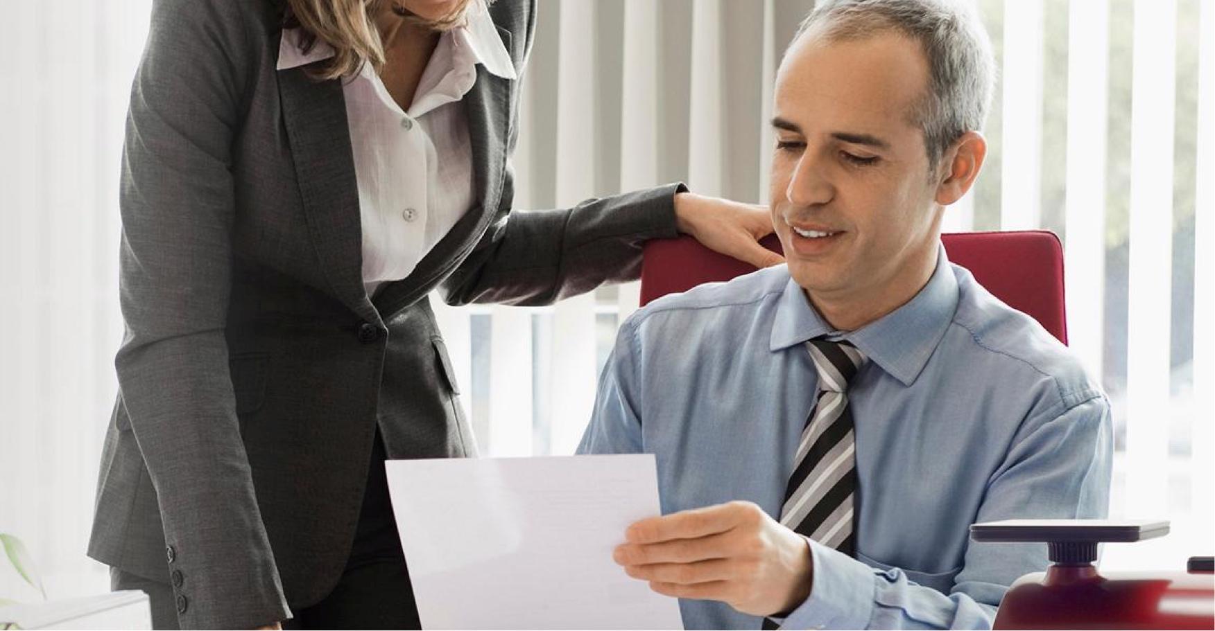 Mann und Frau in Businesskleidung besprechen Dokument