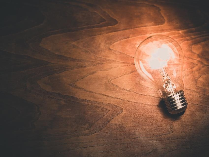 Illuminated light bulb on a piece of wood