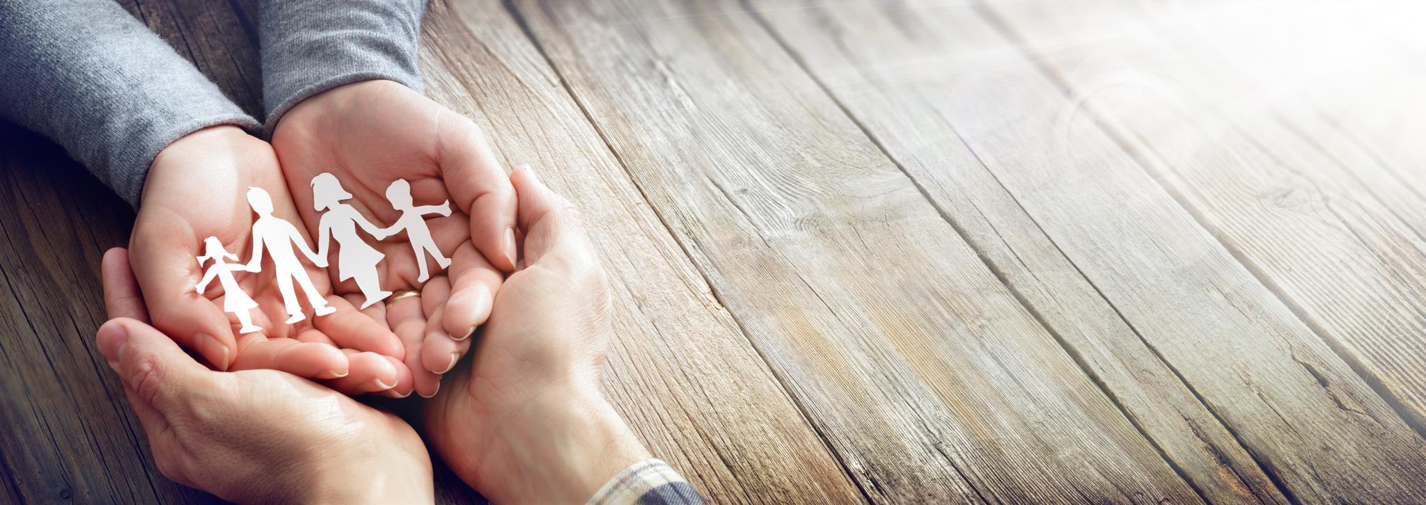 Aus weißem Papier geschnittene Familien-Silhouette liegt auf geöffneten Frauenhänden, die wiederum von Männerhänden gehalten werden