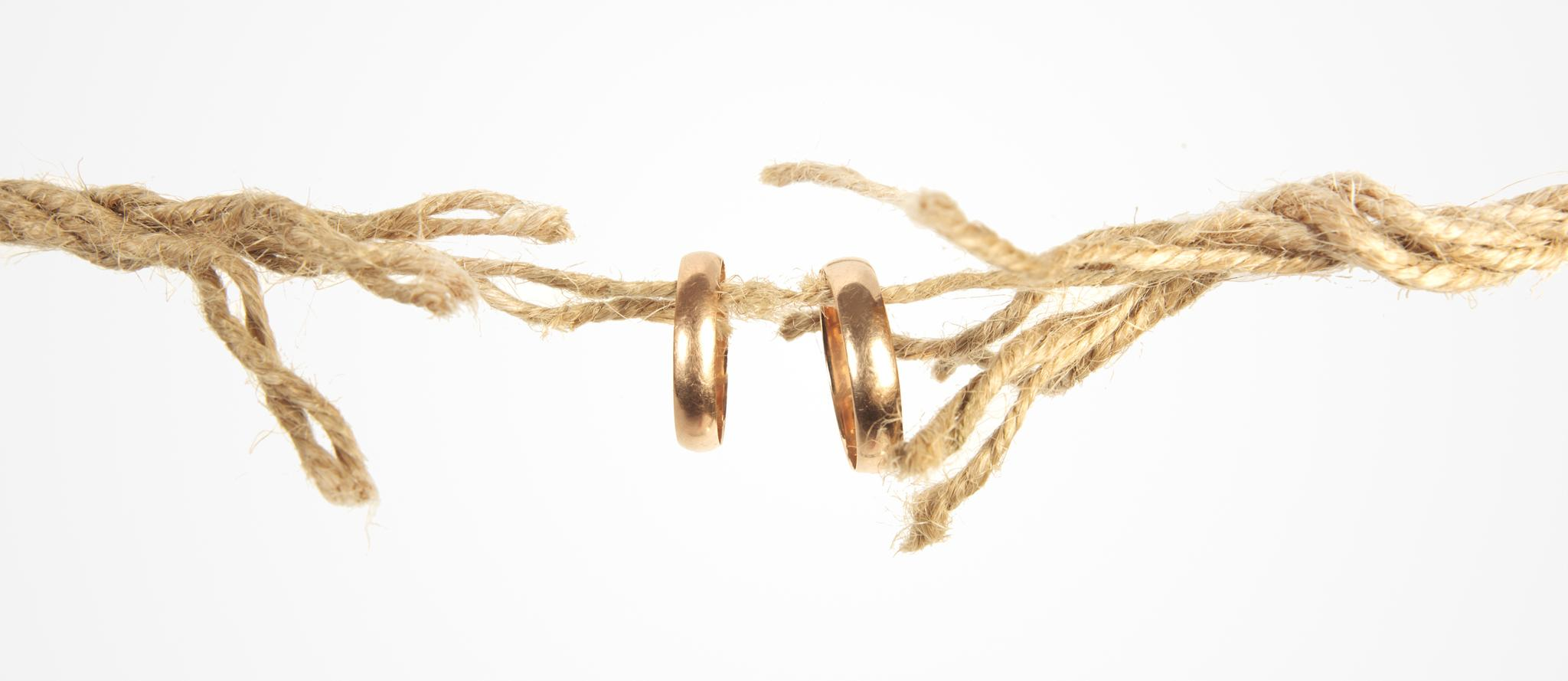 Zwei goldene Eheringe hängen an einem sich auflösenden Seil