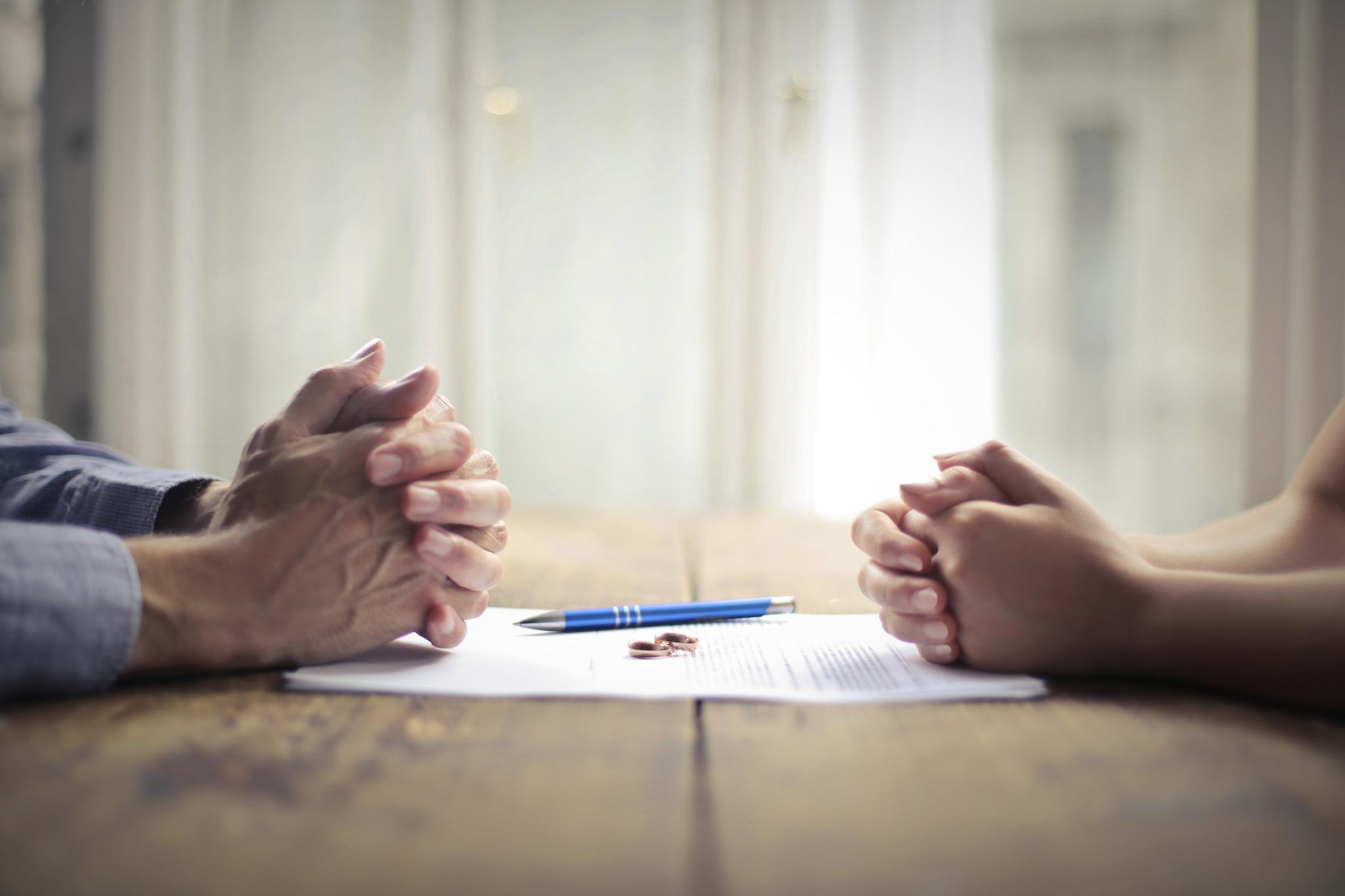 Gefaltete Hände eines Mannes und einer Frau, die sich am Tisch gegenüber sitzen, auf einem Blatt Papier mit Kugelschreiber