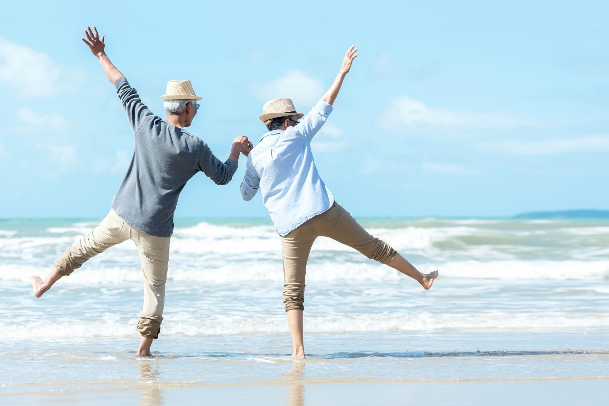 Senioren-Paar springt am Strand
