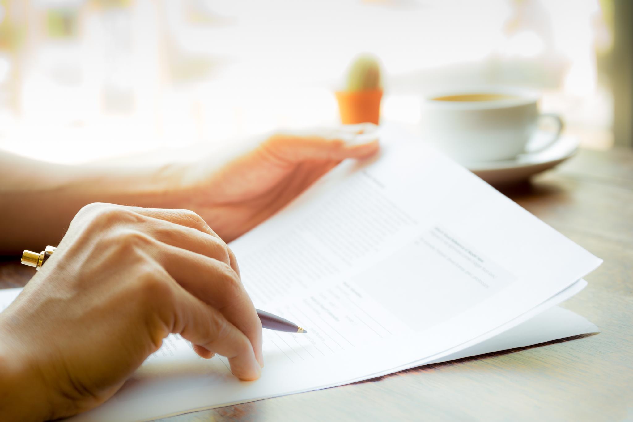Frauenhand mit Kugelschreiber über Briefpapier