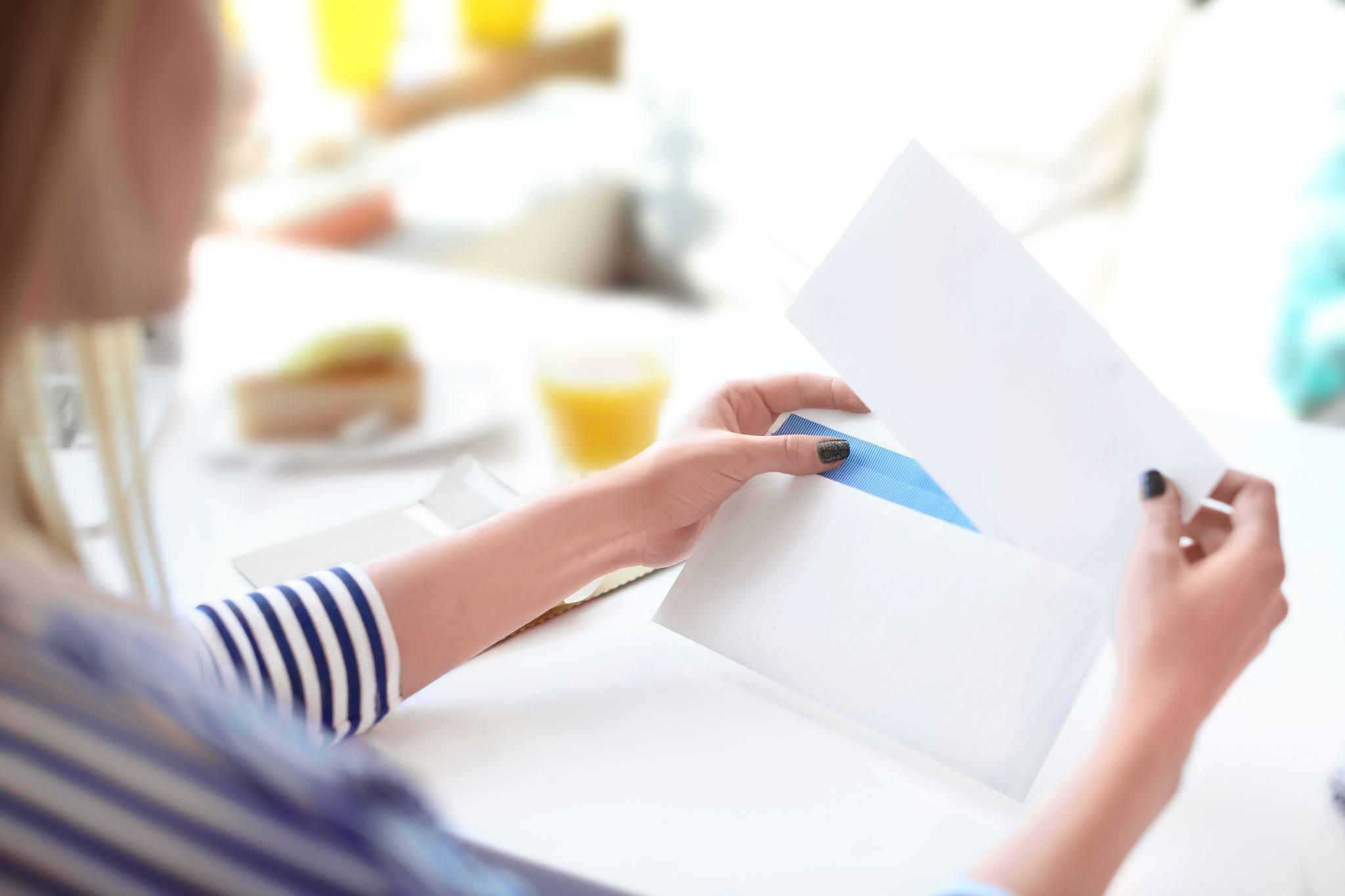 Frau sitzt am Tisch und liest einen Brief