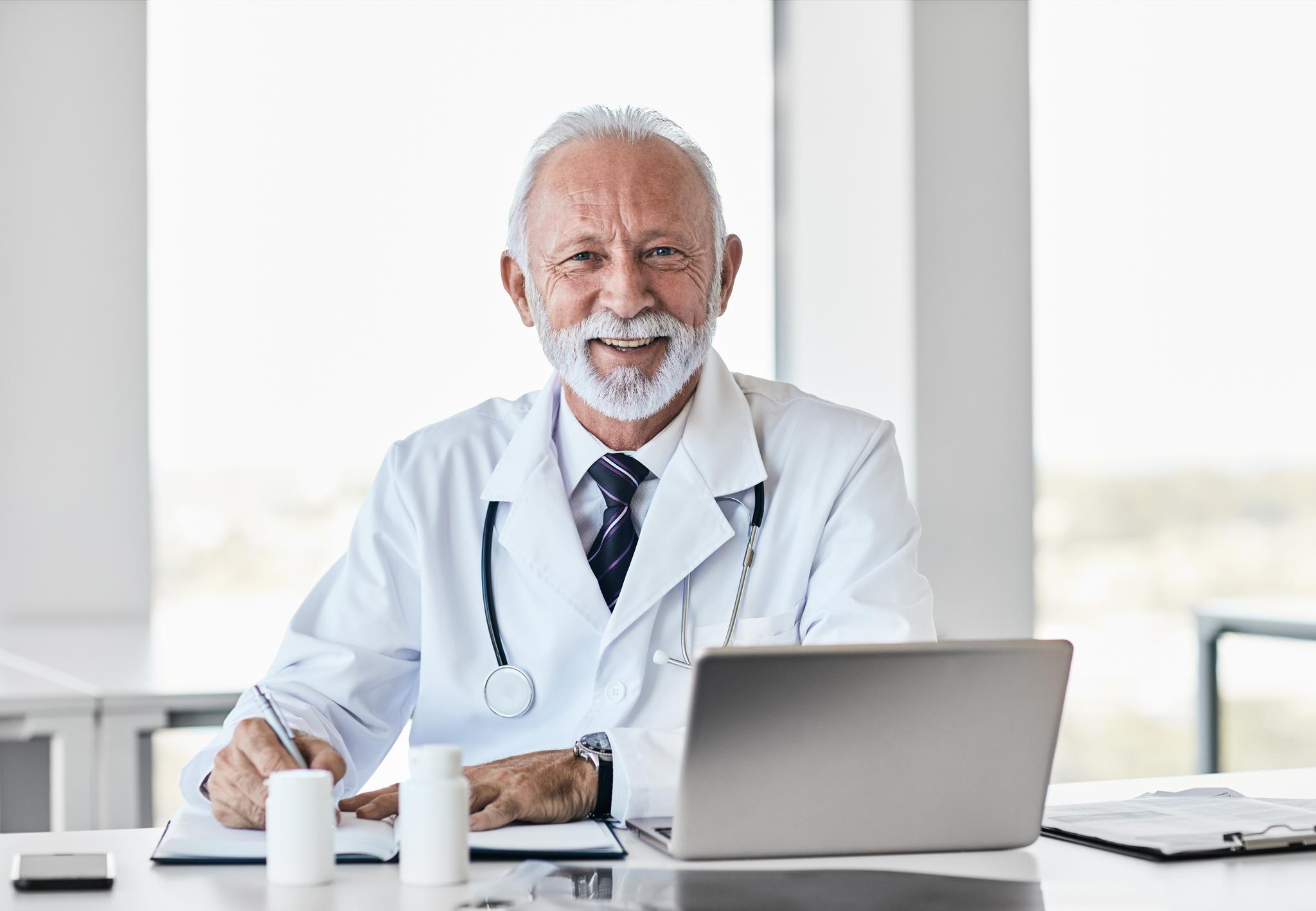 Lachender, älterer Arzt mit weißem Bart sitzt hinter einem Schreibtisch am aufgeklappten Laptop