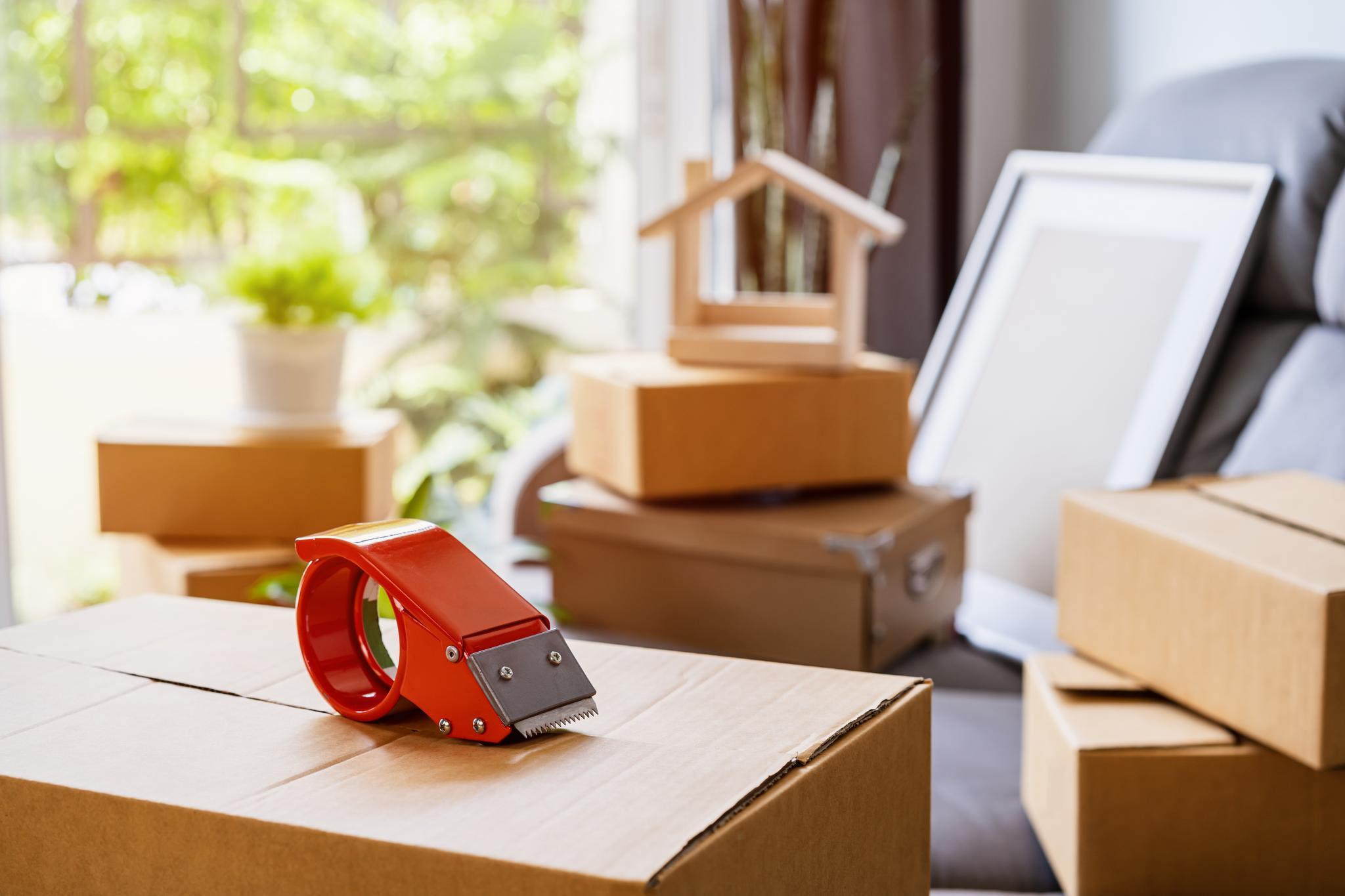 Roter Klebefilmabroller auf Umzugskarton in Wohnzimmer