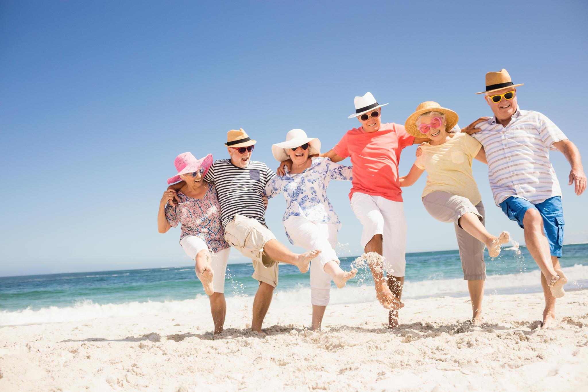 Ausgelassene Menschen bilden tanzend eine Kette am Strand