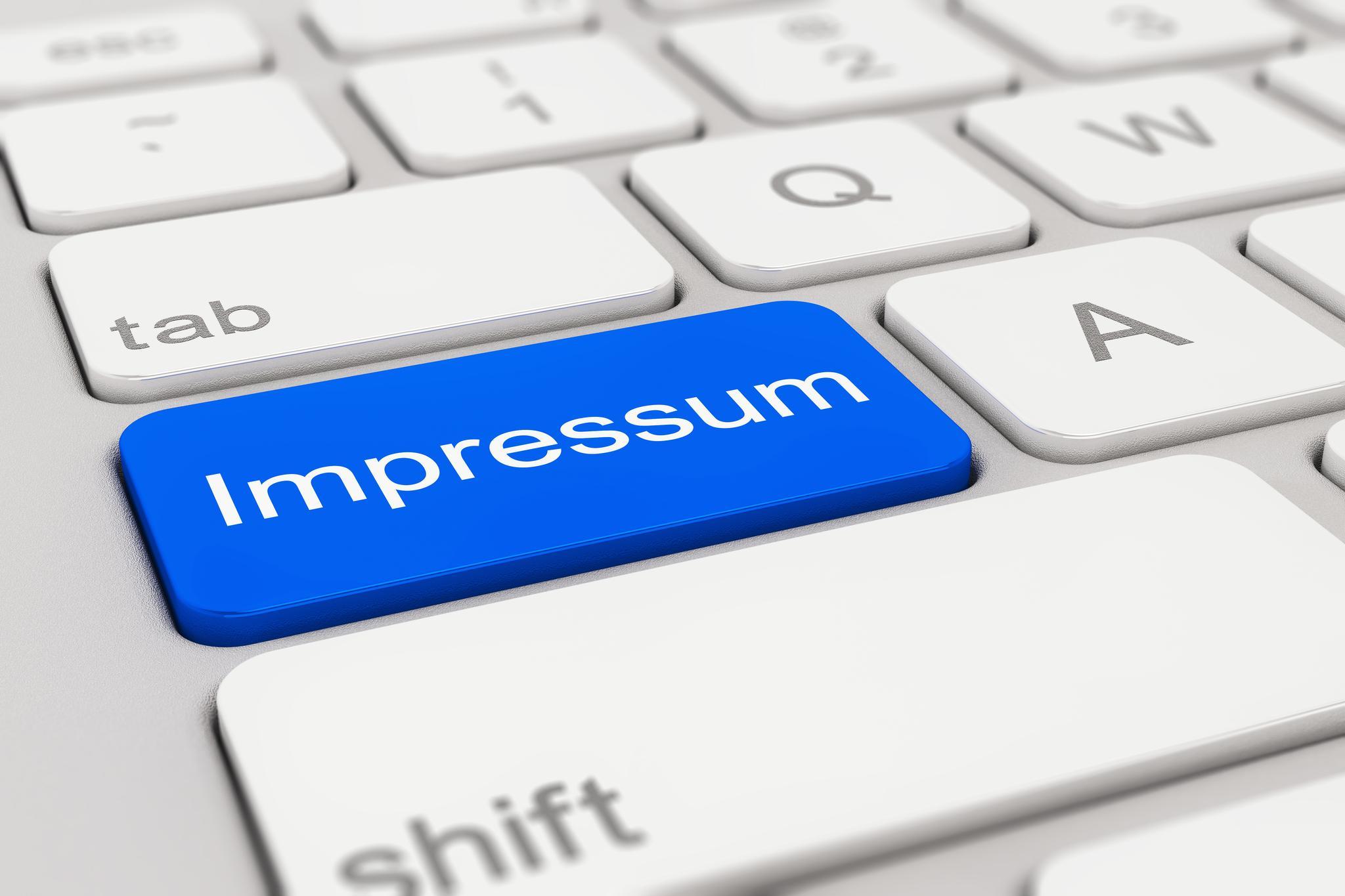 weiße PC-Tastatur mit blauer Taste und Schriftzug Impressum