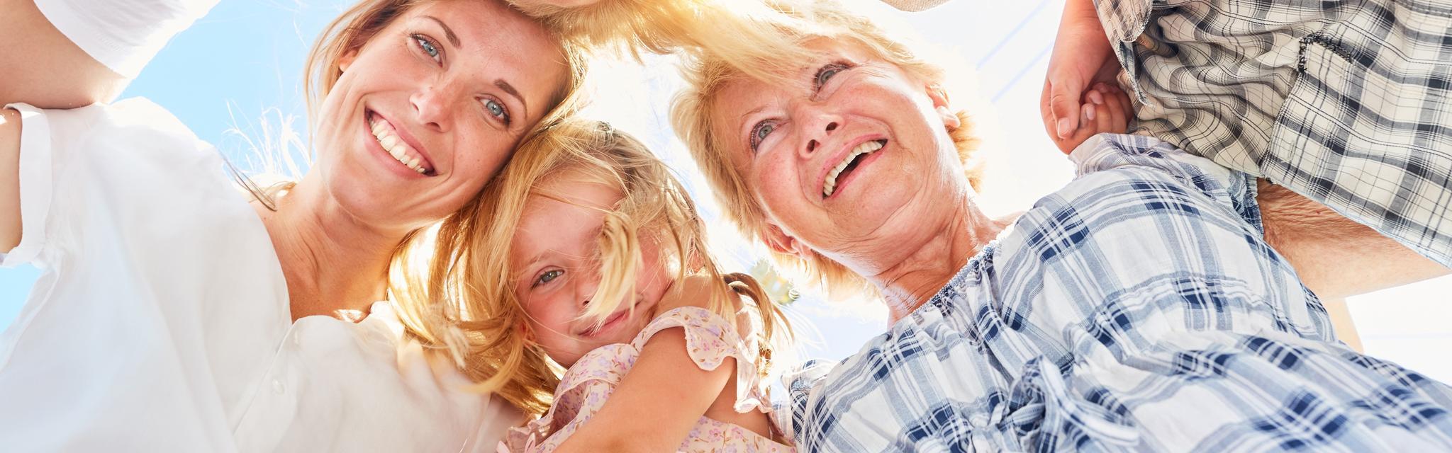 Lachende Eltern, Kinder und Großeltern fassen sich im Kreis an den Schultern