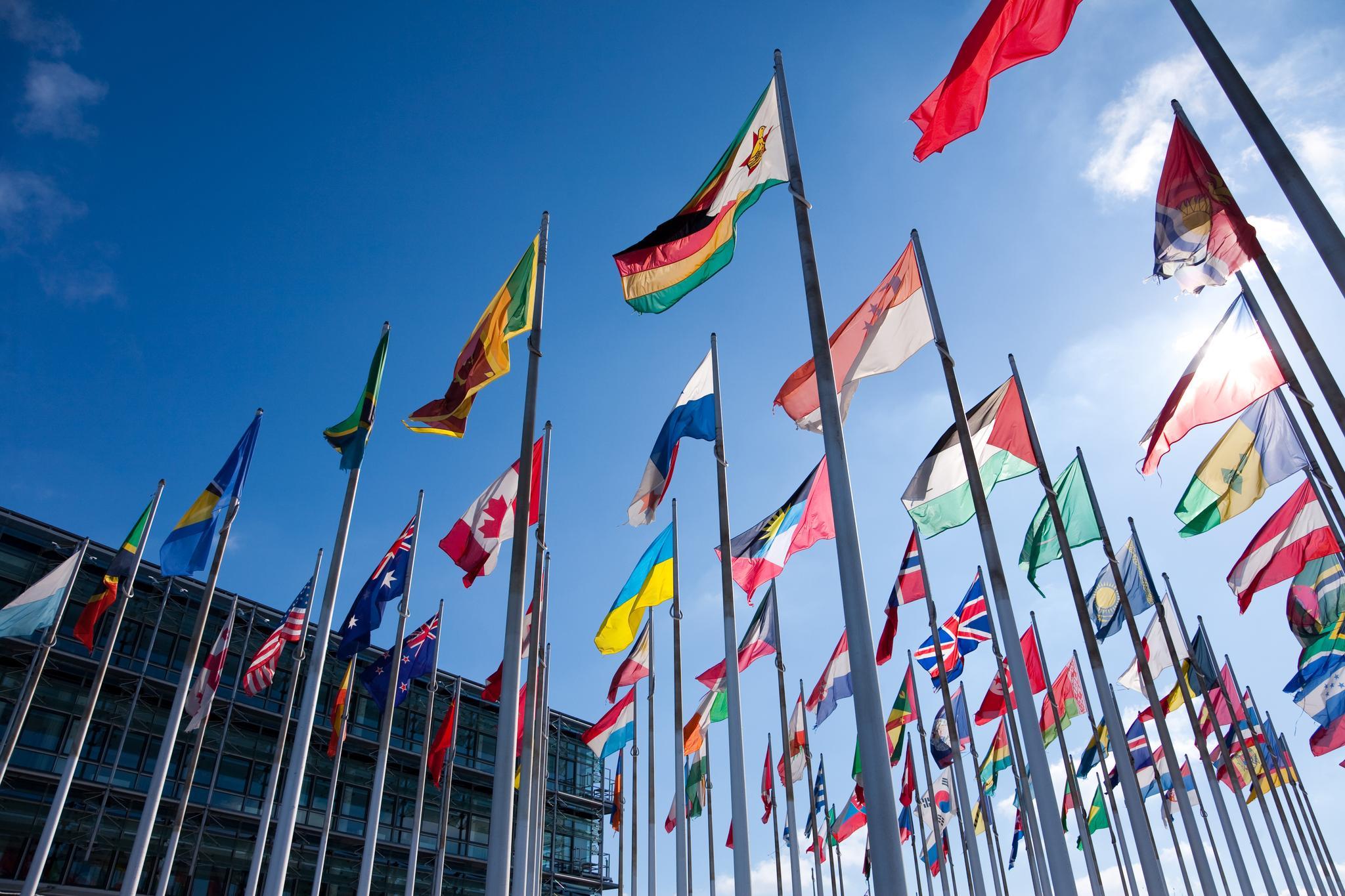 Fahnenmasten mit internationalen Flaggen vor blauem Himmel