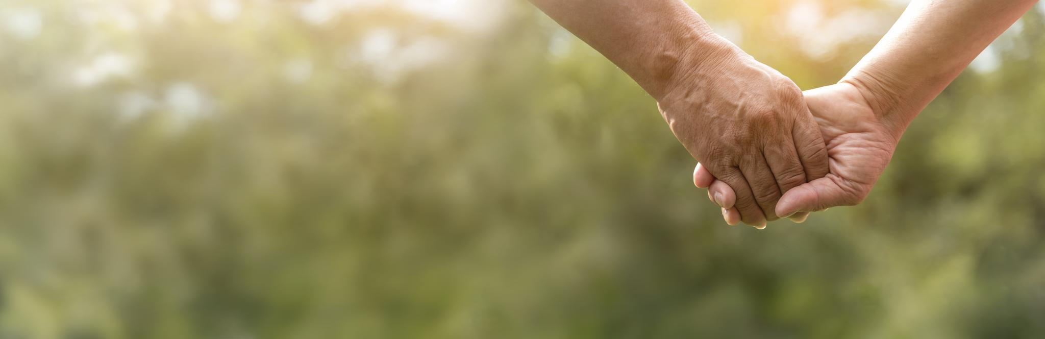 Ausschnitt: Zwei Senioren halten sich an den Händen