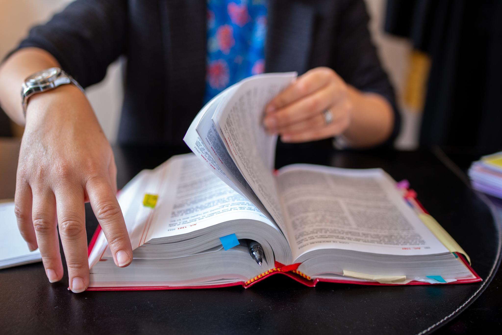 Jemand blättert in einem dicken, aufgeschlagenen Buch mit Markierungen