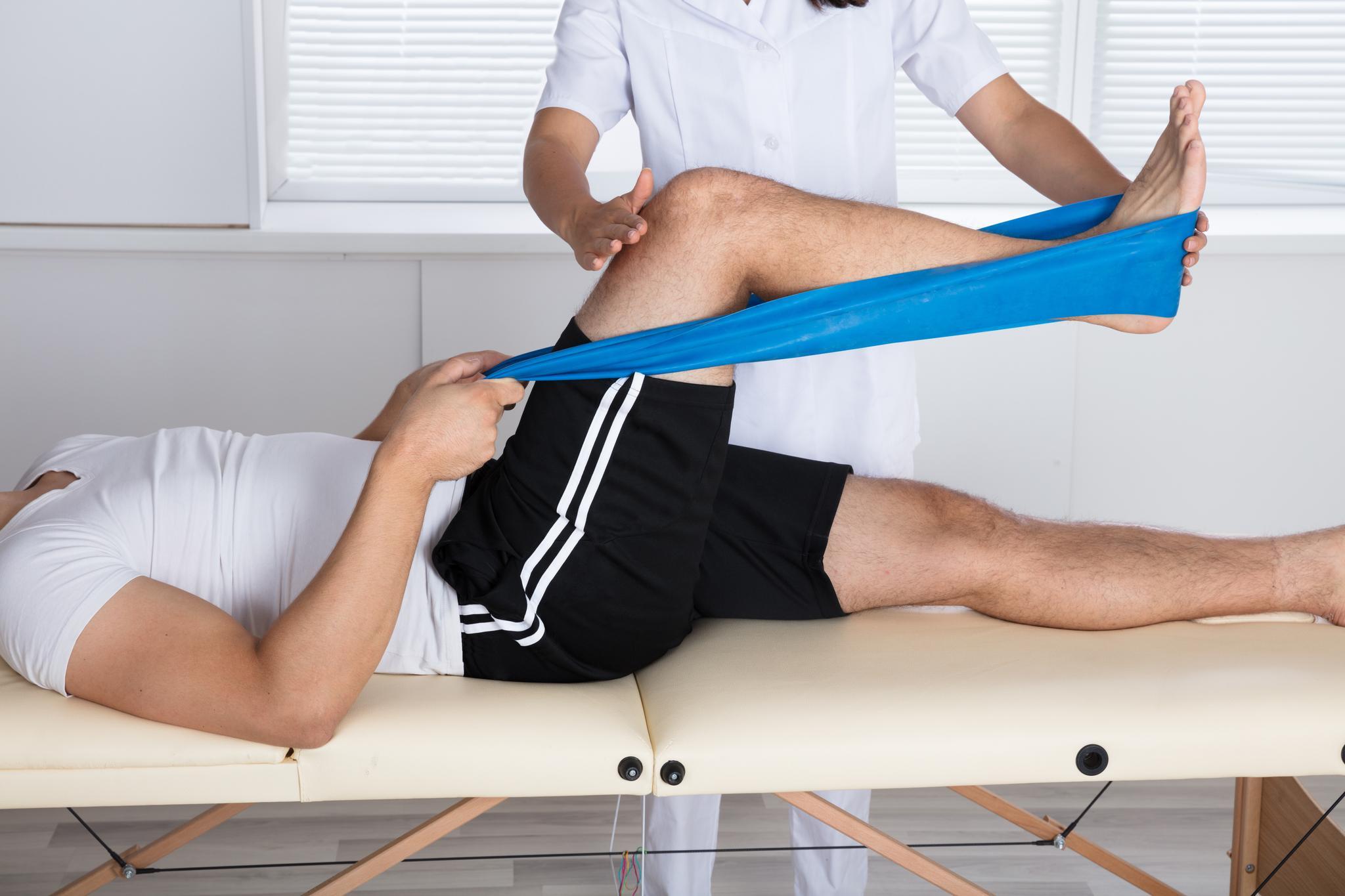 Mann trainiert sein Bein auf der Liege eines Physiotherapeuten