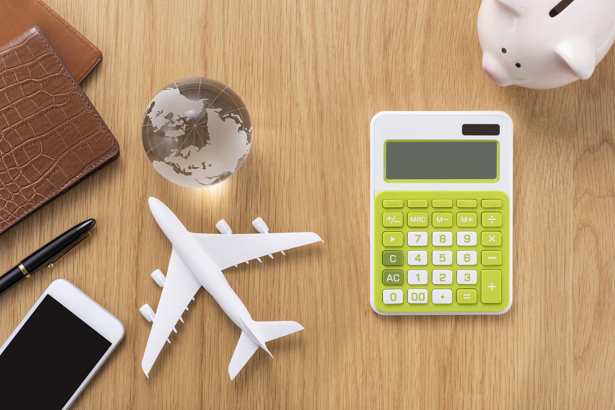 Taschenrechner, Glaskugel, weißes Spielzeug-Flugzeug, Handy, Sparschwein und Kugelschreiber auf Holztisch