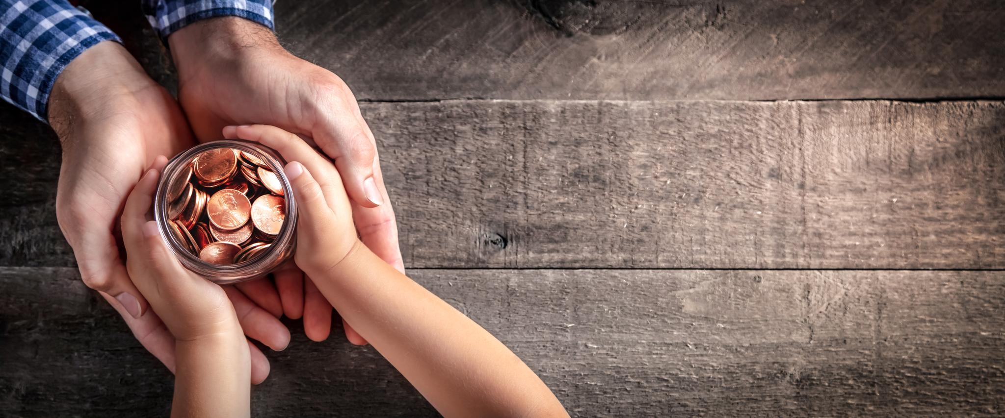 Die Hände eines Erwachsenen halten Kinderhände, die ein Glas mit Münzen umschließen