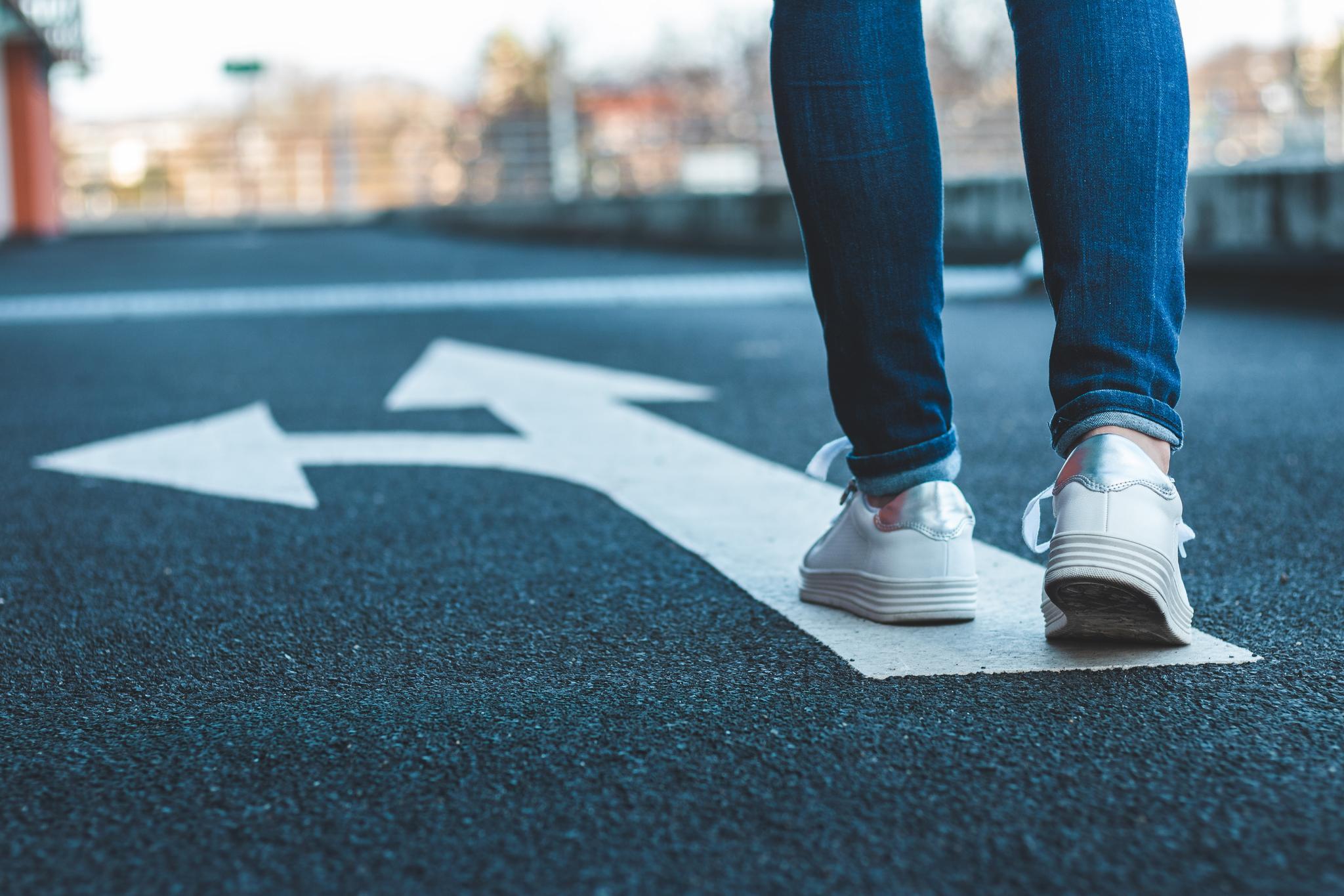 Zwei Beine in Jeans und Turnschuhen auf Straßenabschnitt mit Richtungspfeilen