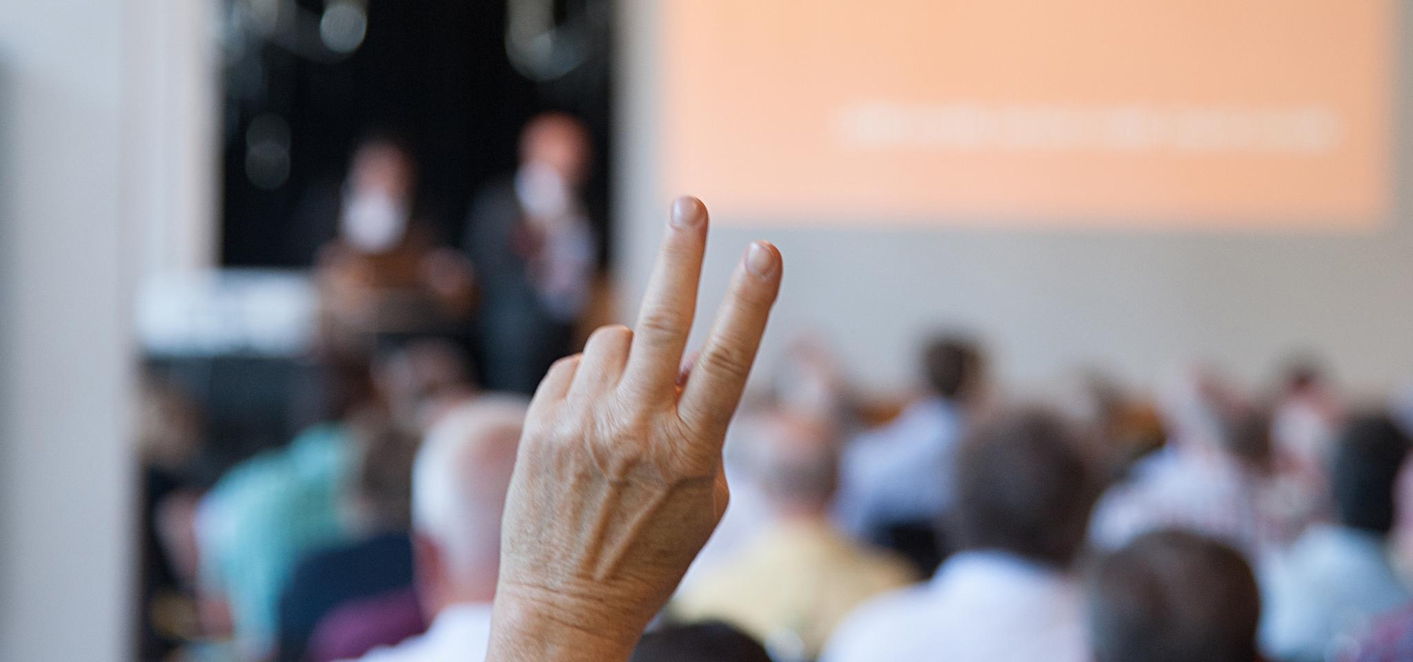 Handzeichen mit zwei ausgestreckten Fingern bei einer Abstimmung