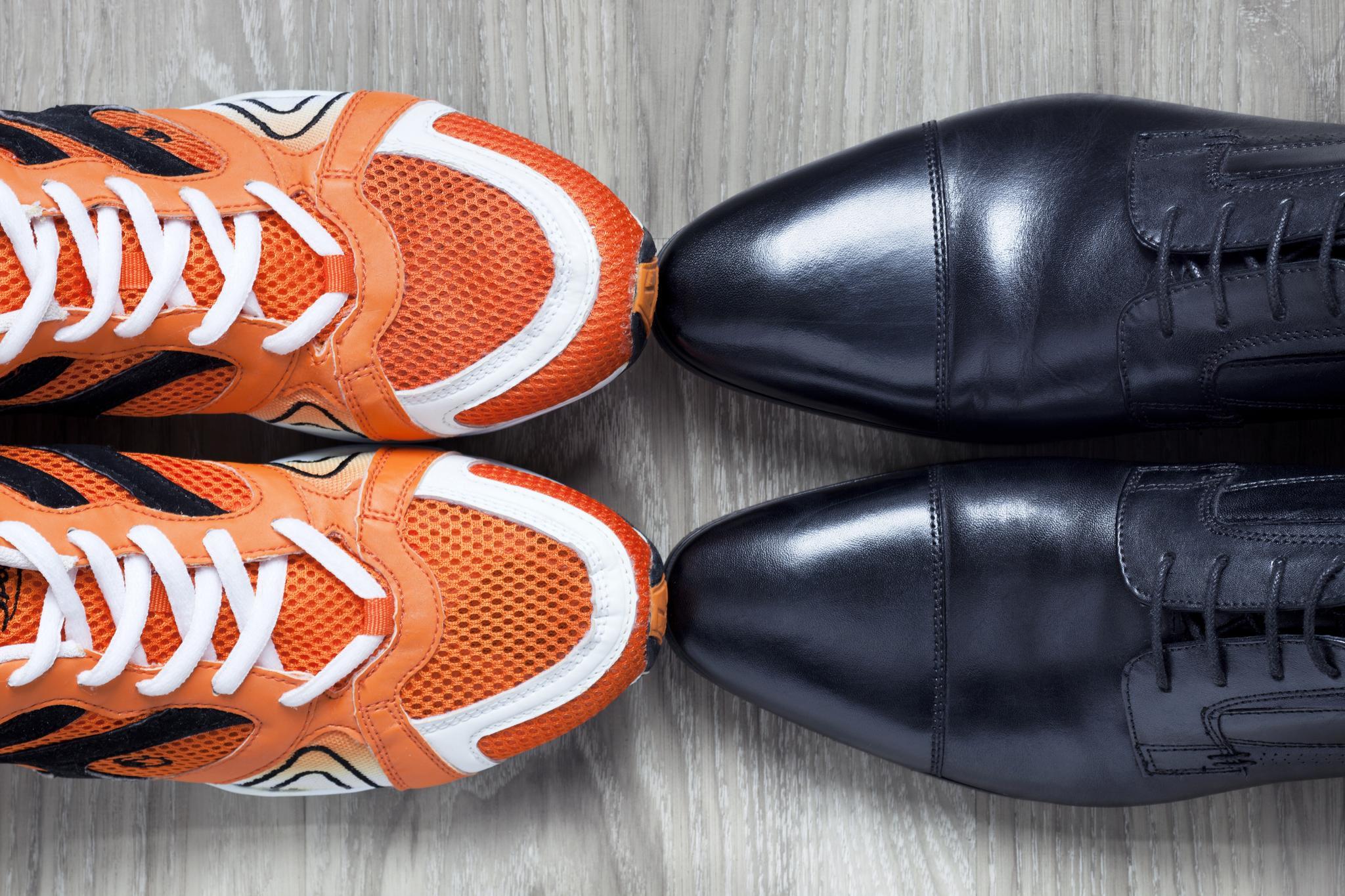 Orange Turnschuhe stehen Spitze an Spitze mit schwarzen Businessschuhen