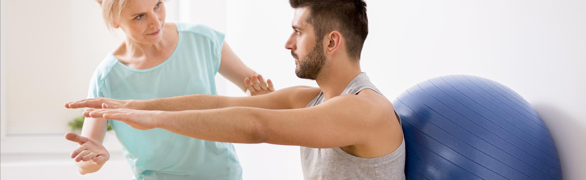Mann und Frau bei physiotherapeutischer Behandlung mit Ball