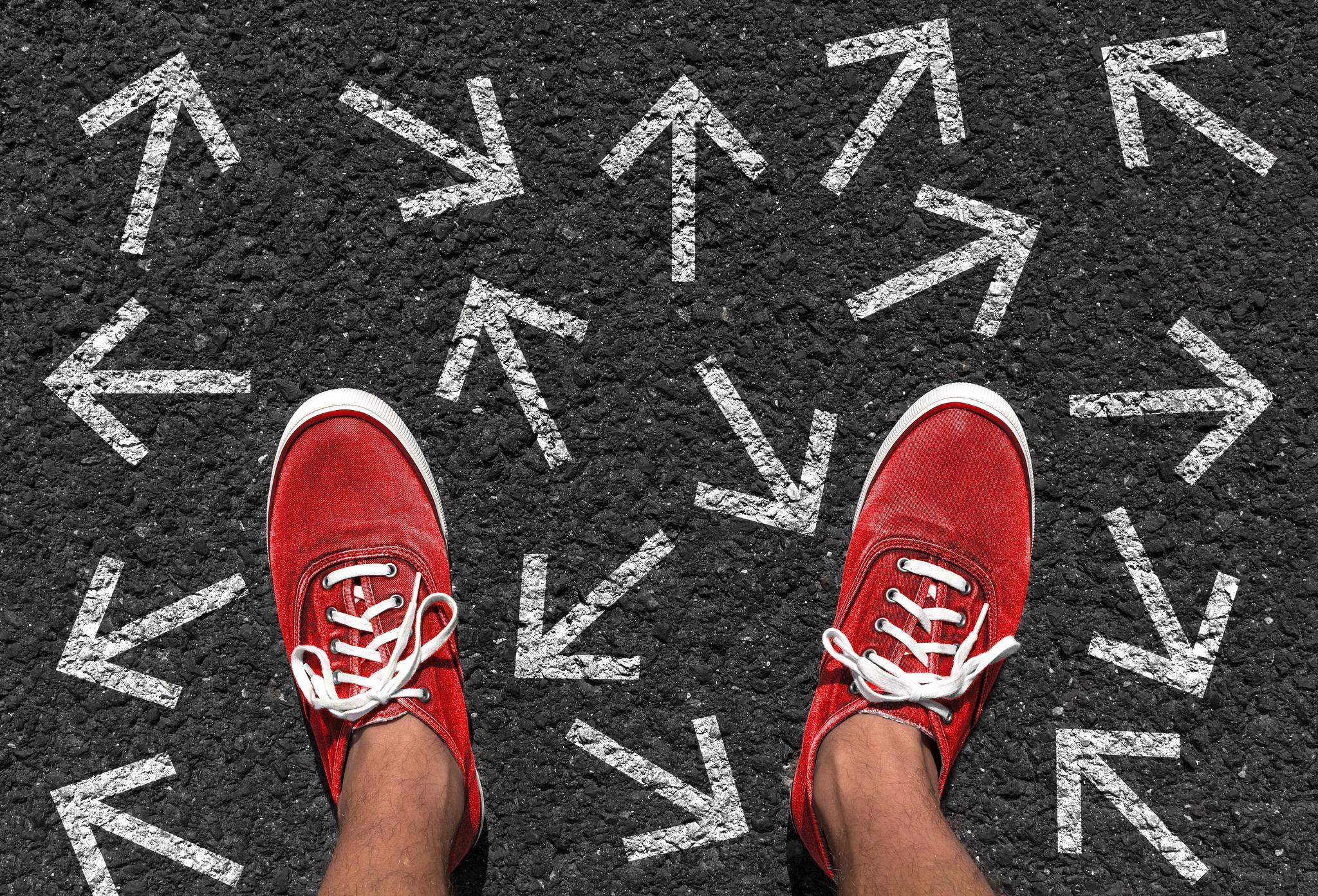 Ein Paar Füße in roten Turnschuhen auf Asphalt, auf dem weiße Pfeile in verschiedene Richtungen zeigen