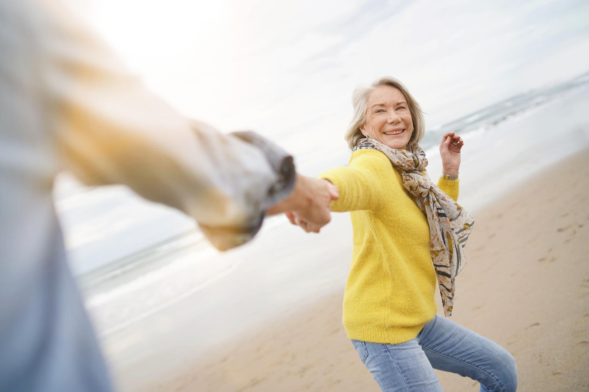 Lachende Frau am Strand wird von Mann an der Hand gezogen