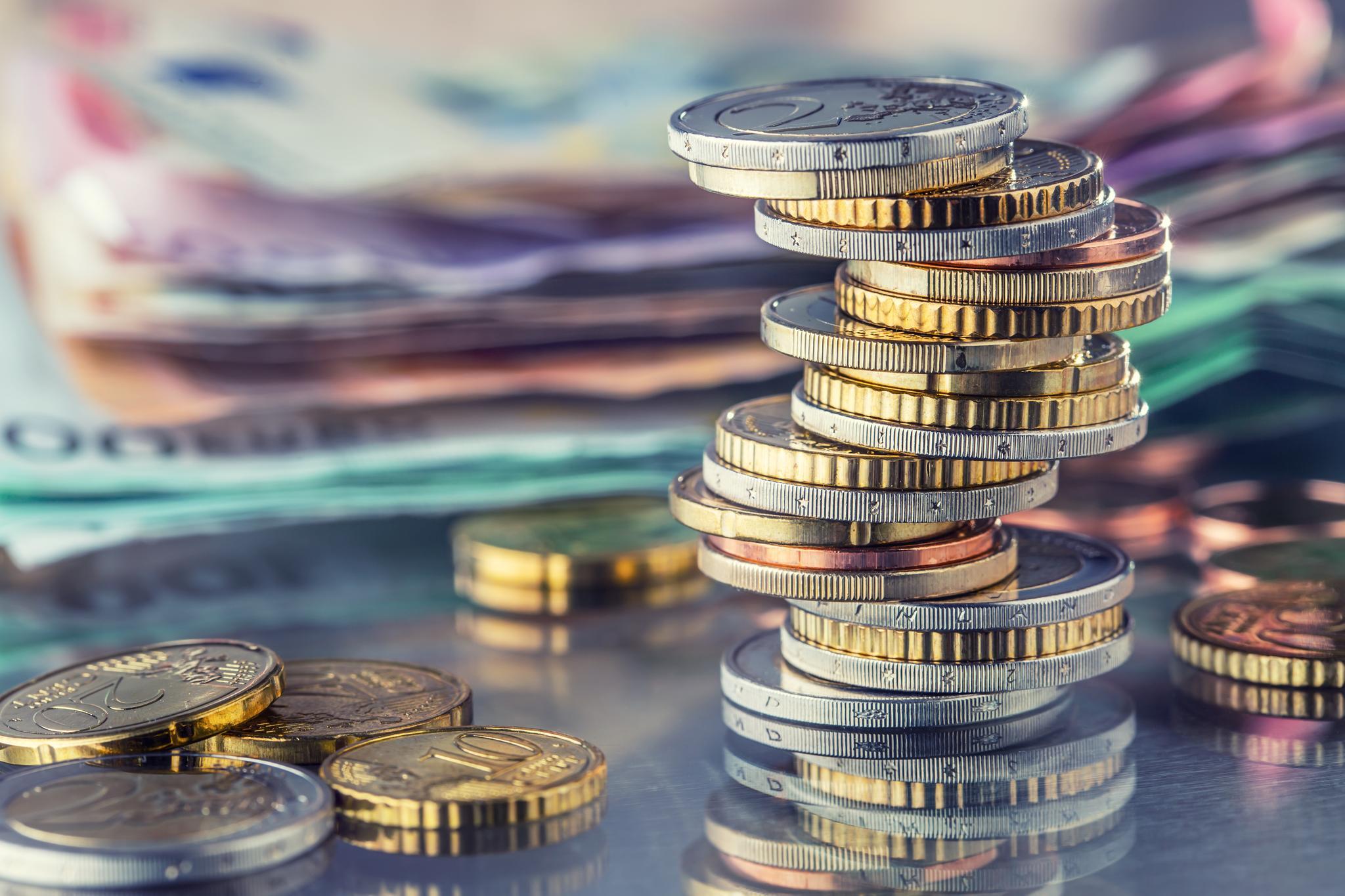 Gestapelte Euro-Münzen mit Euro-Scheinen im Hintergrund
