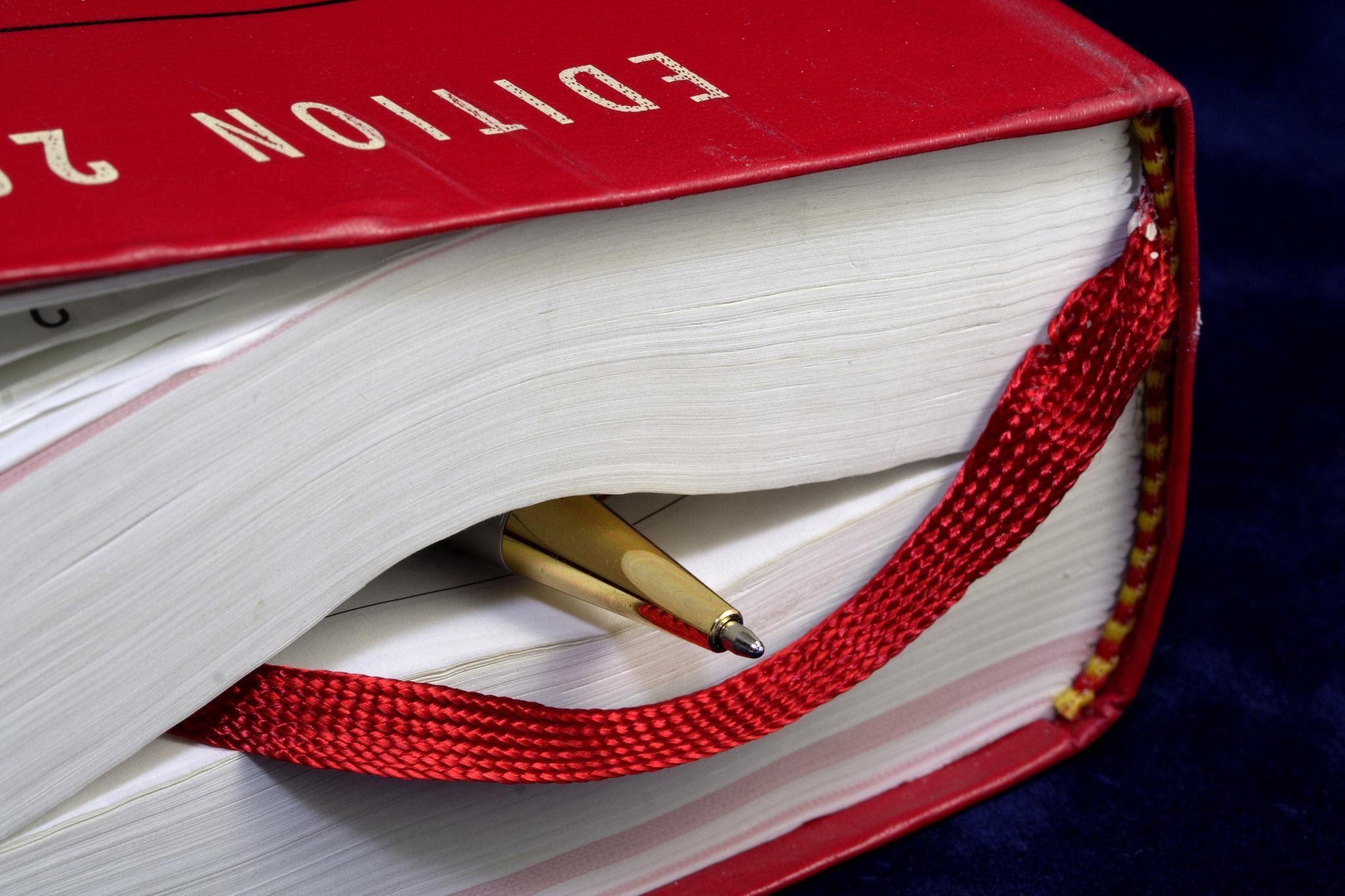 Goldfarbener Kugelschreiber und rotes Lesezeichenband in dickem Gesetzbuch eingeklemmt
