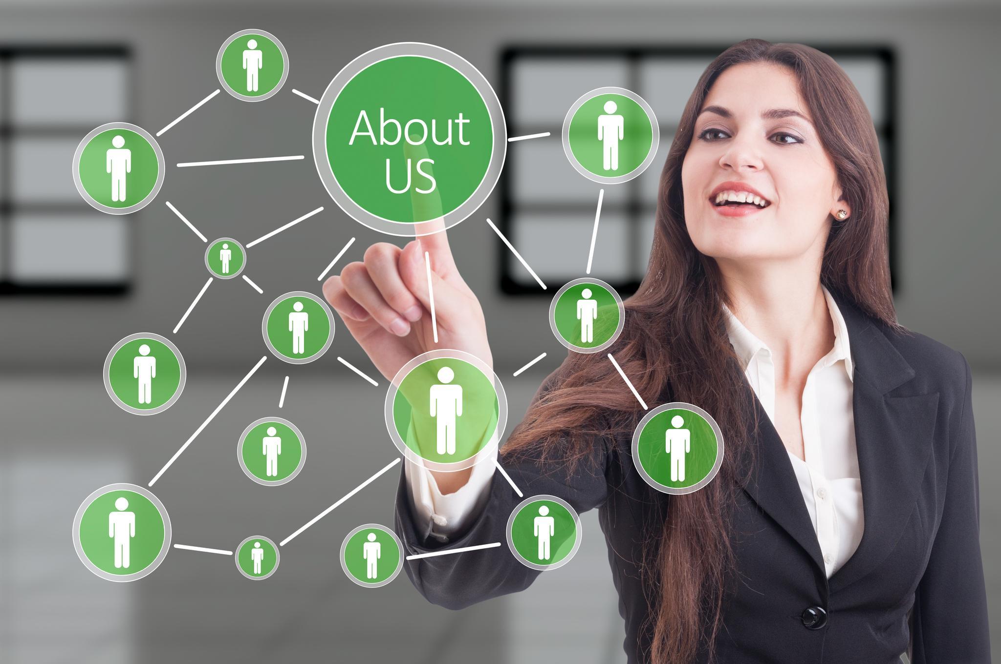 """Frau zeigt auf grünen Kreis, in dem """"About us"""" steht, und der durch Linien mit anderen Kreisen verbunden ist, die Icons in Menschenform zeigen"""