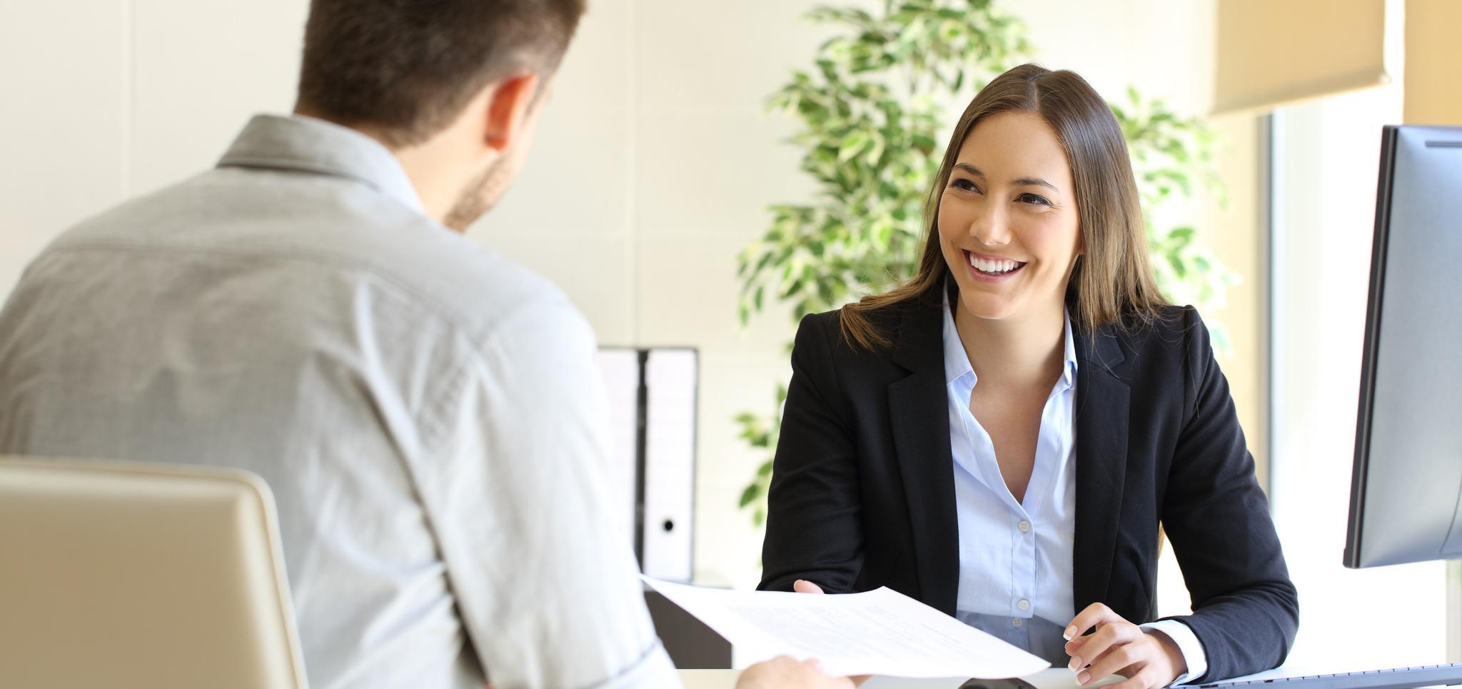 Lächelnde Frau am Schreibtisch im Gespräch mit einem Mann