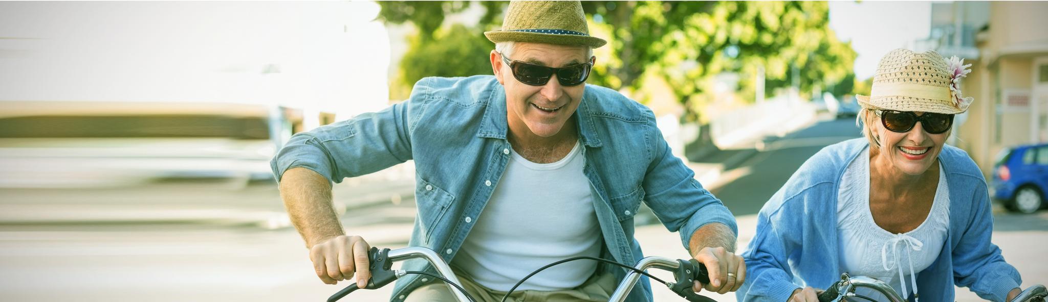 Seniorenpaar mit Hut und Sonnenbrille fährt Fahrrad um die Wette