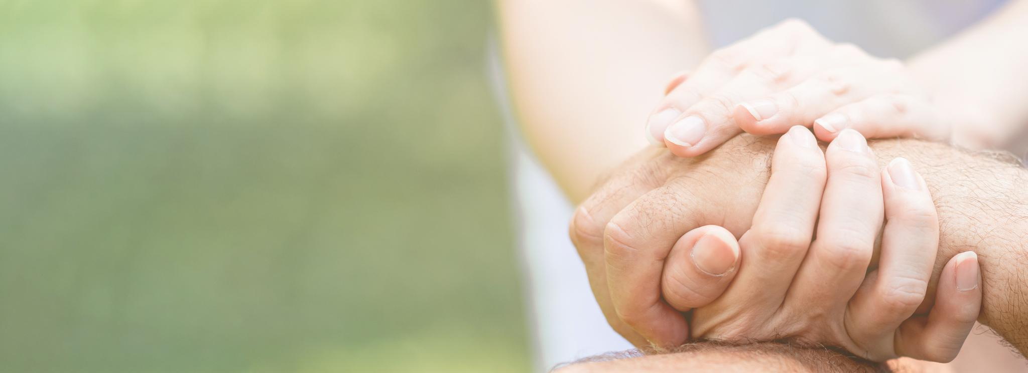 Zwei Hände einer Person umfassen die Hand eines anderen