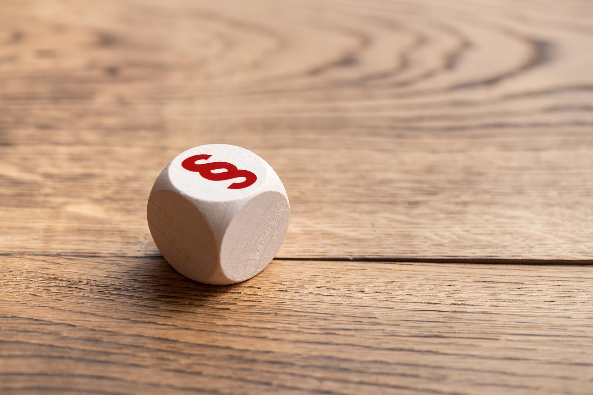 Weißer Würfel mit rotem Paragraphen-Zeichen auf Holztisch