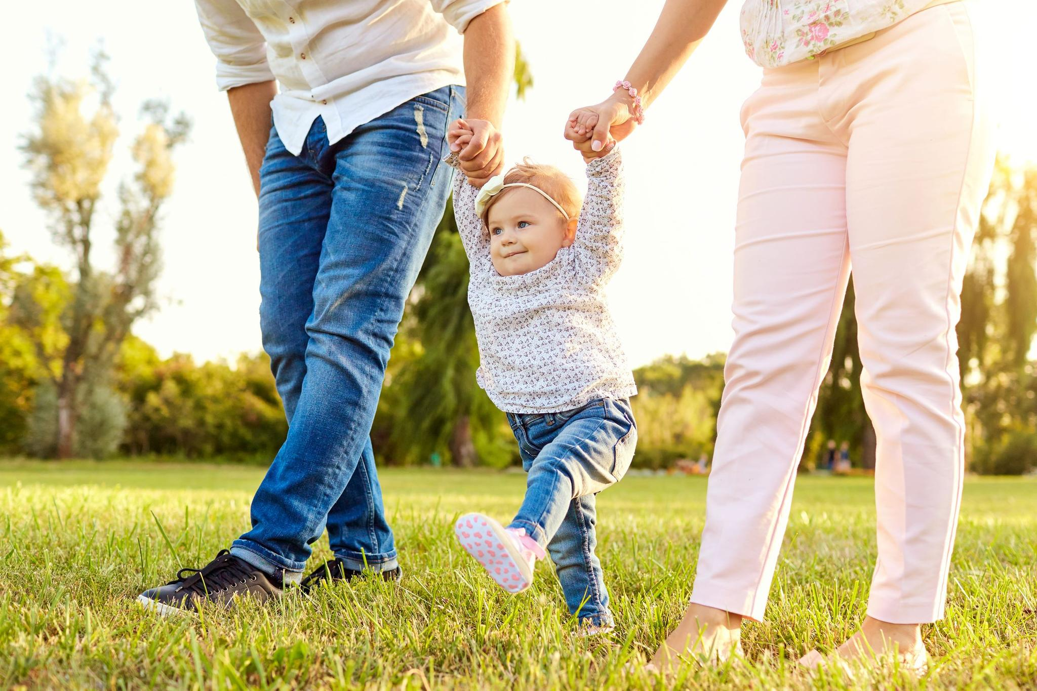 Kleines Mädchen macht erste Schritte an den Händen eines Mannes und einer Frau