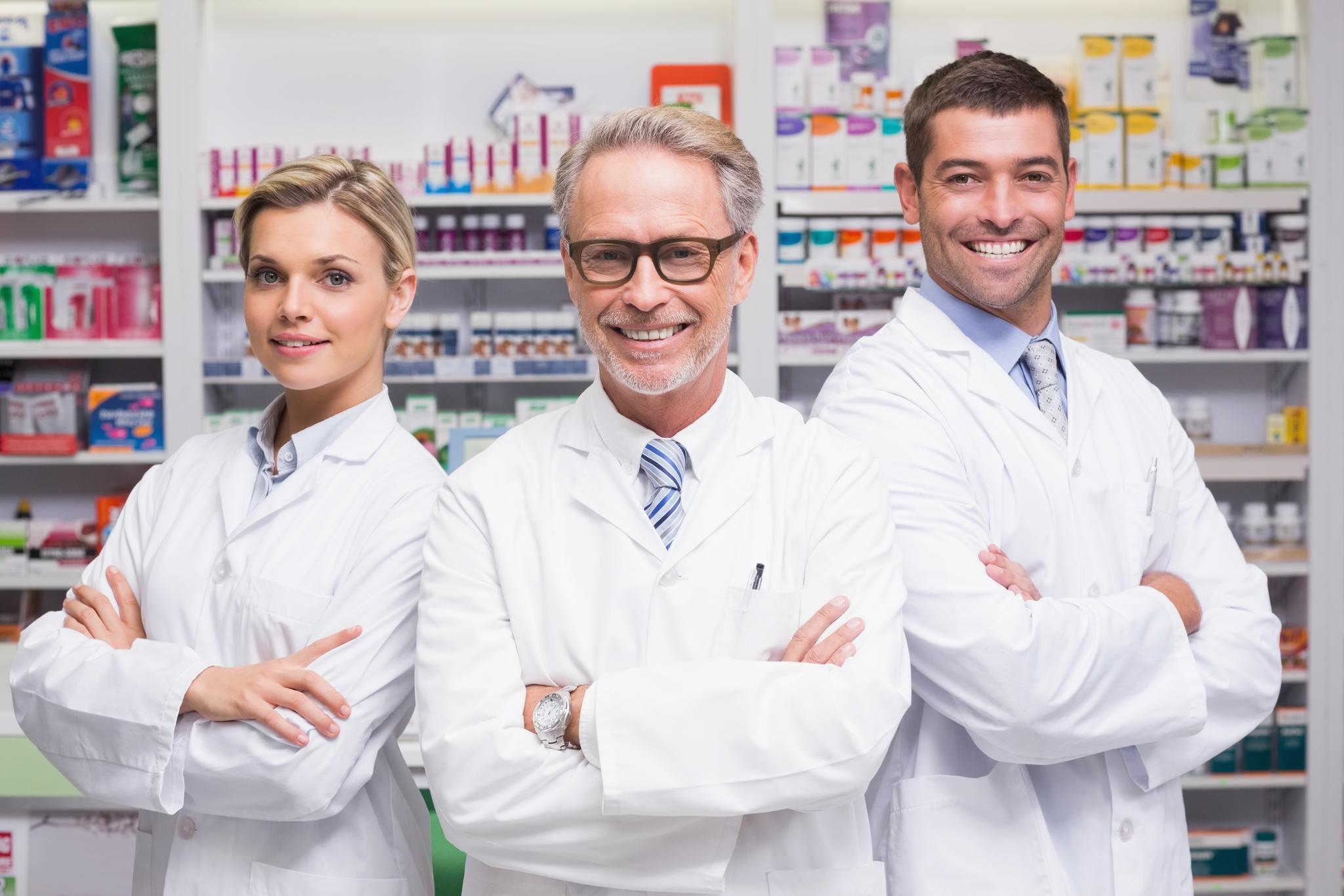 eine Apothekerin und zwei Apotheker stehen vor einem Regal und lächeln