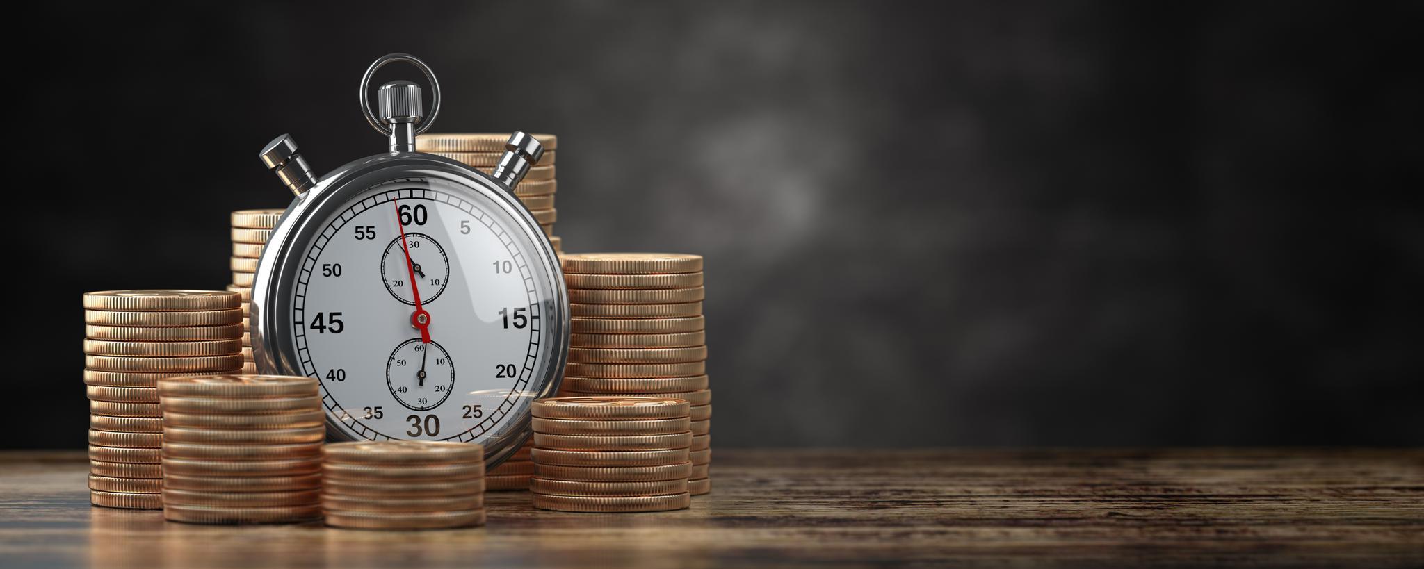 Stoppuhr zwischen aufgestapelten Münzen