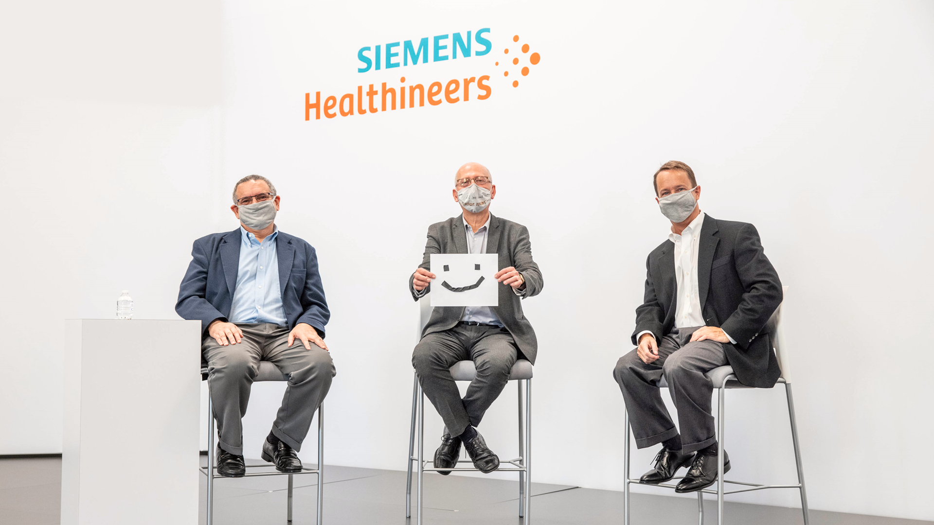 Scientists and physicians at Siemens Healthineers show their enthusiasm for Biograph Vision Quadra by holding up a smiling face.