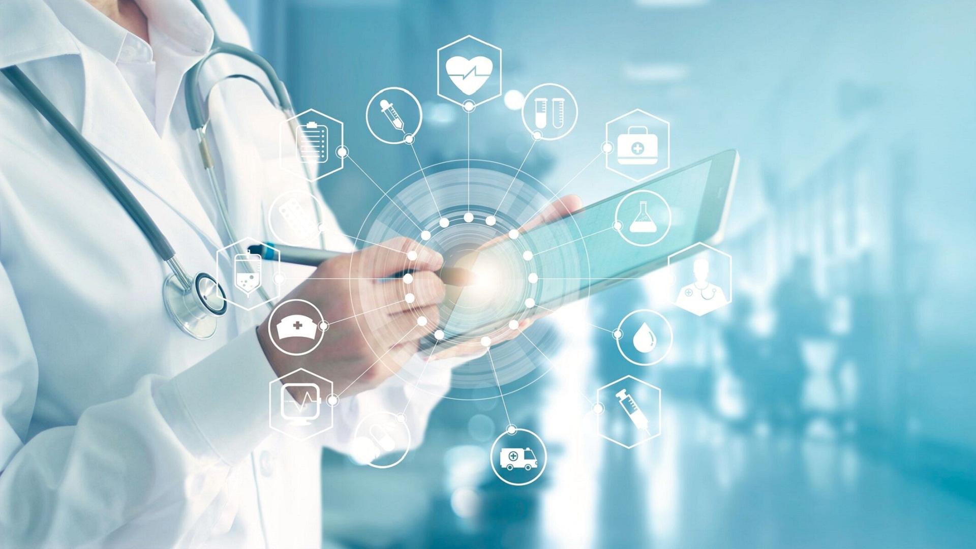 futuristic image of a doctor holding a tablet and different healthcare related app symbols visualized around the clinicians' hand