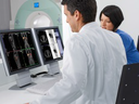 Two doctors using a Molecular Imaging system interface