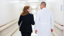 Male physician and hospital manager walking in hospital hall.
