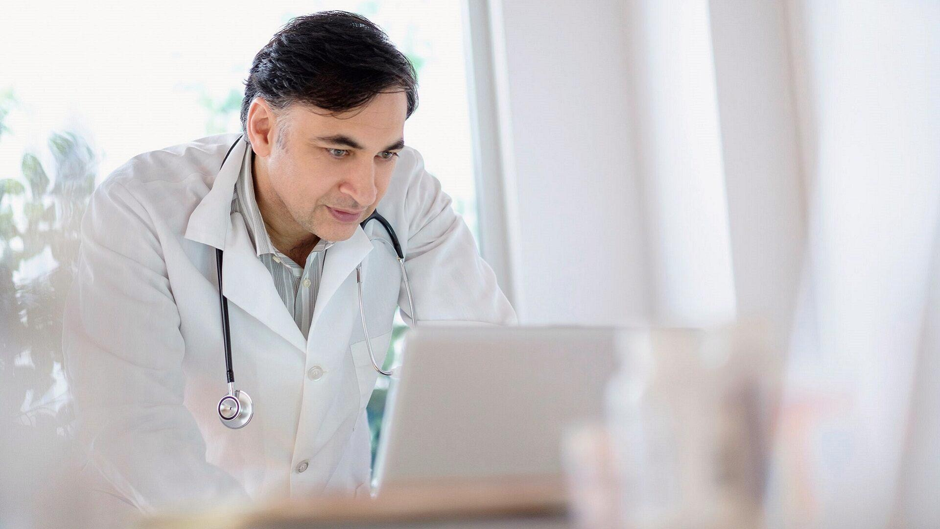 doctor is looking at a laptop screen