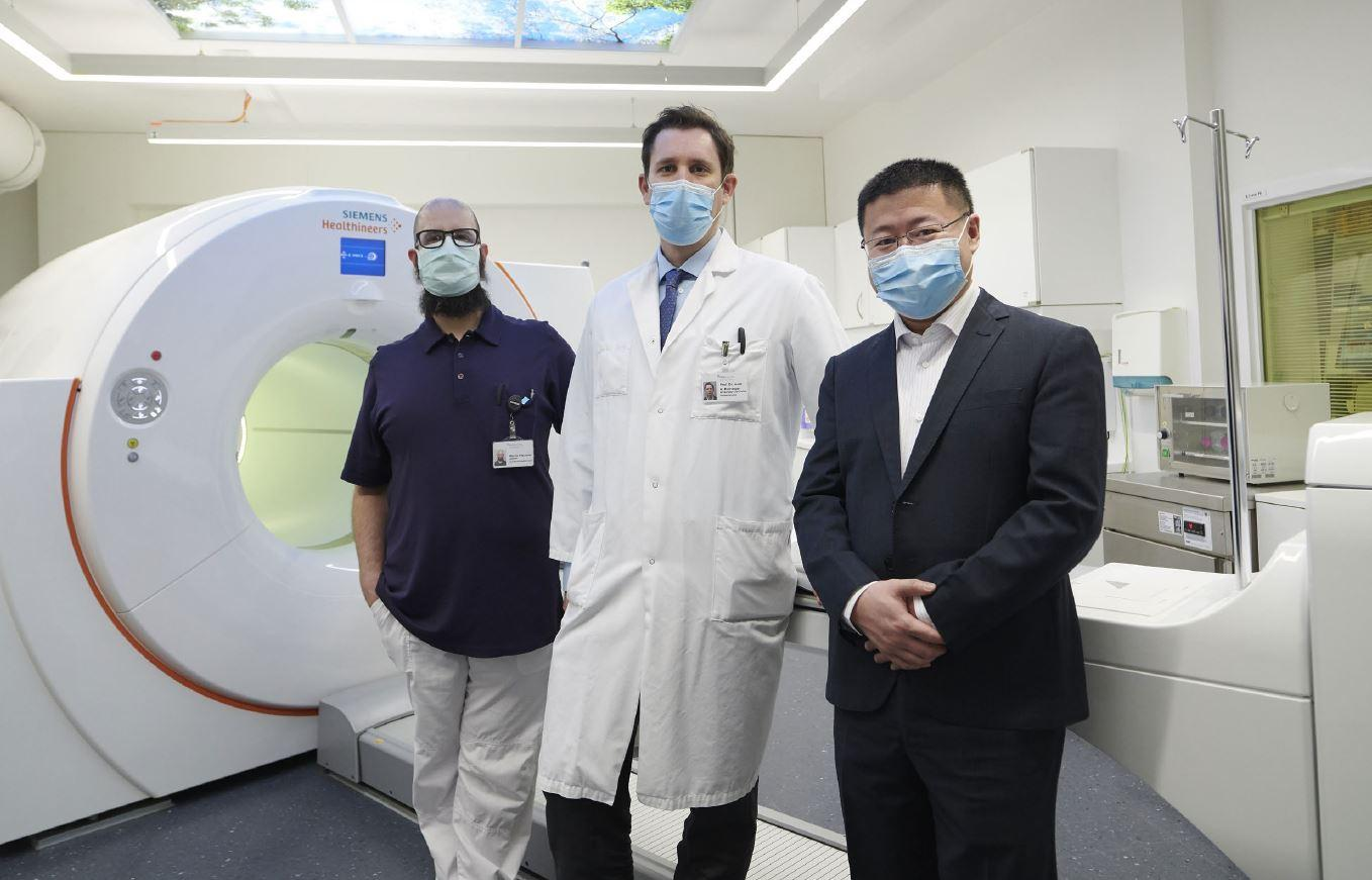 Marco Viscione ; Axel Rominger, MD, PhD ; and Kuangyu Shi, PhD stand in front of their department's whole-body molecular imaging PET/CT system : Biograph Vision Quadra.