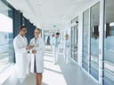 Several healthcare professionals interacting in a corridor