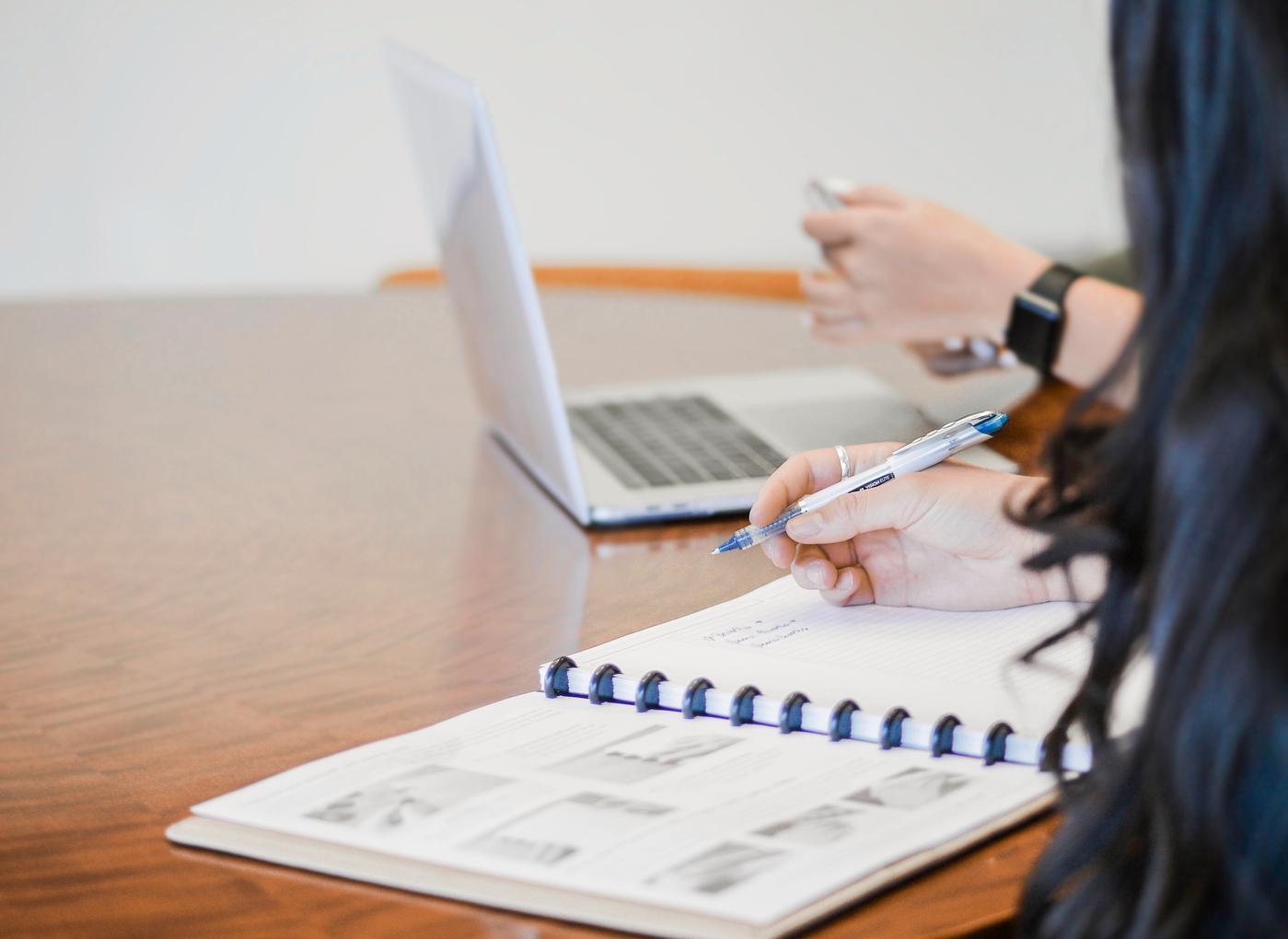 Frau schreibt in einen Kalender