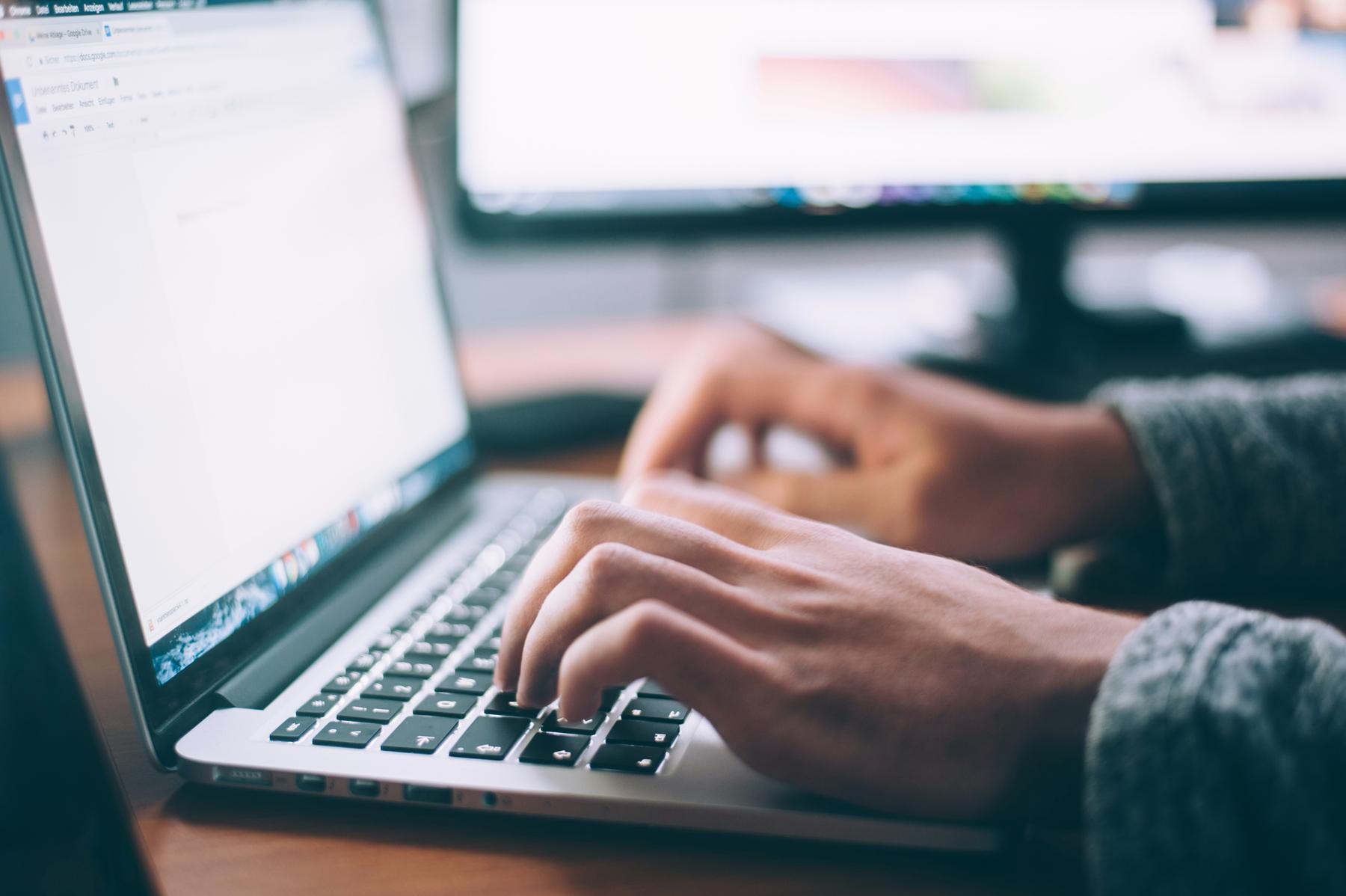 Mann tippt am Laptop - man sieht nur die Hände und den Bildschirm