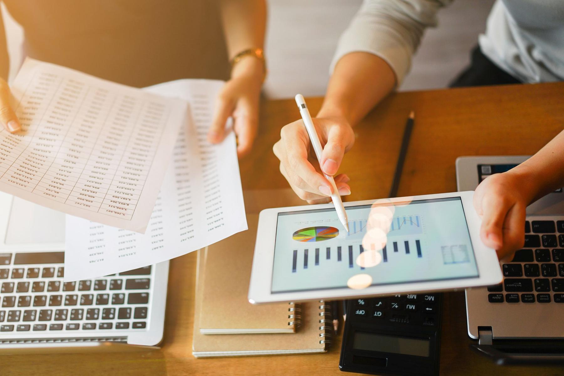 Tablet mit Auswertungsapp, Schreibtisch mit Laptops