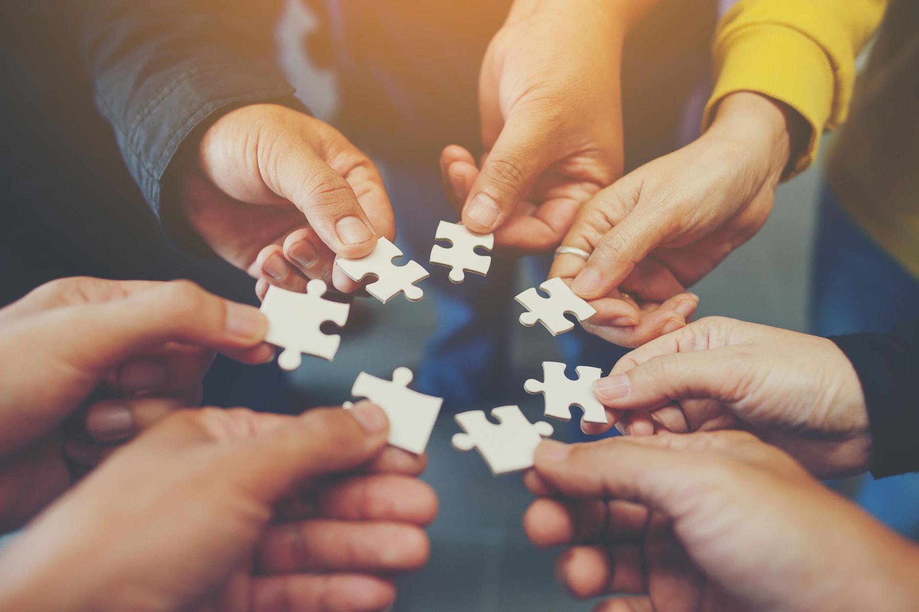 Einzelne Puzzle-Elemente gehalten von Personen zu einem Kreis