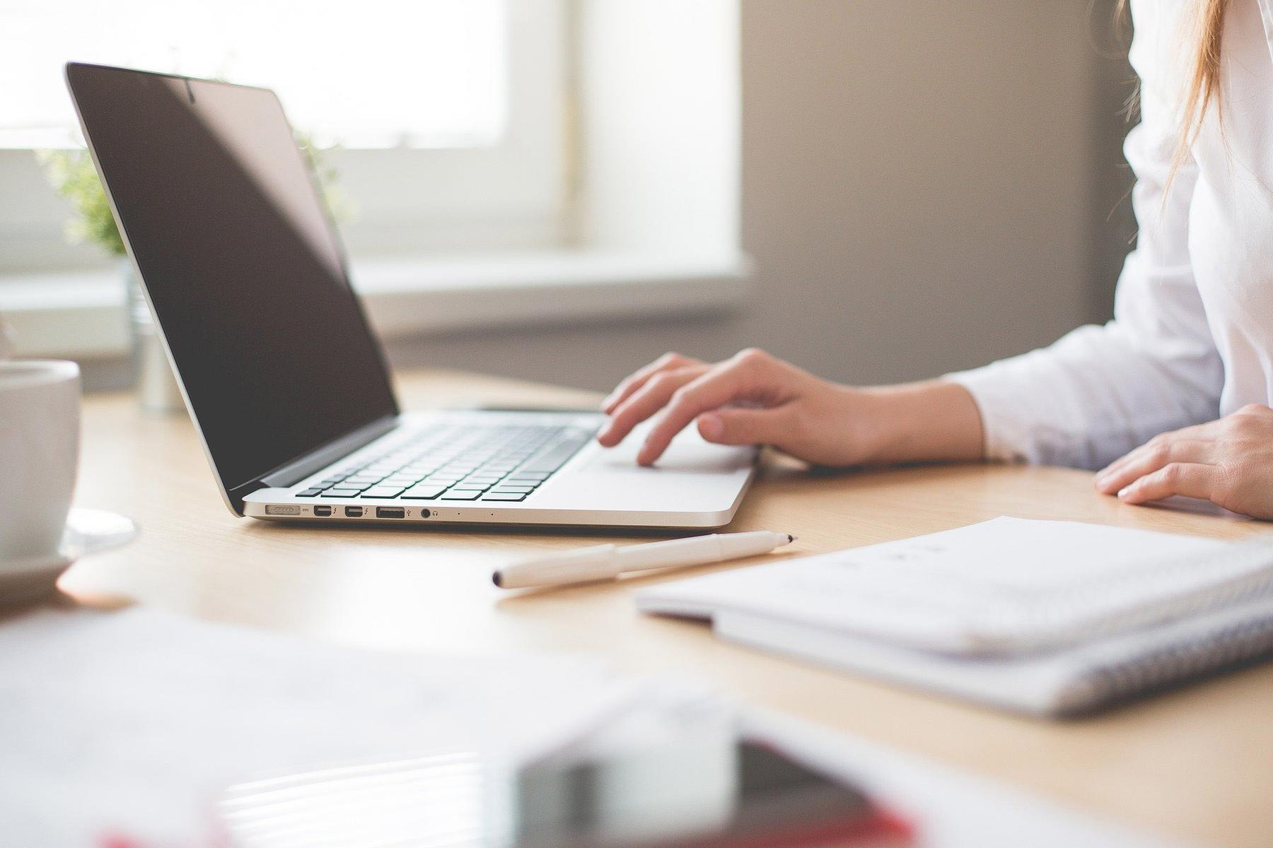 Frau an Laptop mit Notizblock