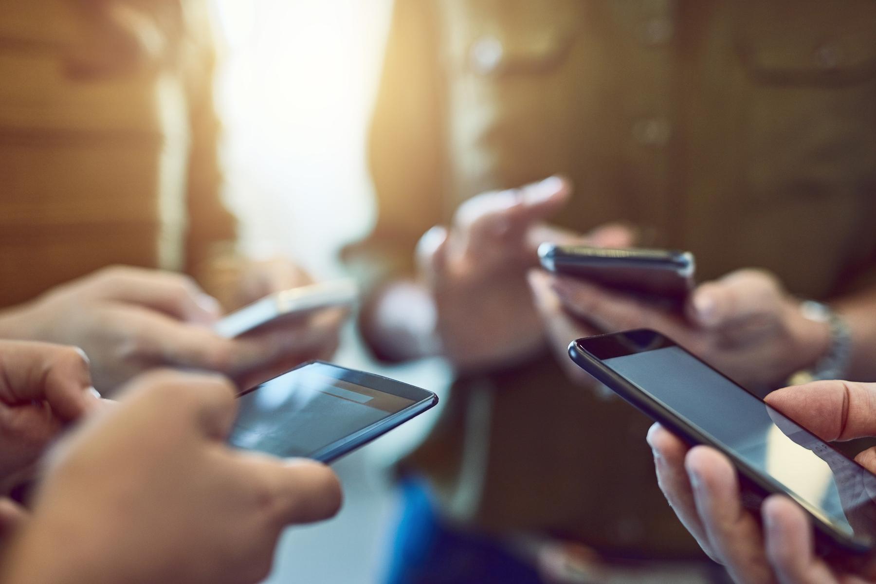 Personen stehen im Kreis und halten ihr Handy's in der Hand