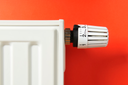Alter Heizkörper mit Thermostat vor rotem Hintergrund