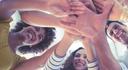 Das Bild zeigt mehrere Personen, die zusammen stehen. Alle strecken Ihre Arme gen Gruppenmitte.